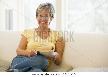 Woman Relaxing With Book In Living Room And Smiling