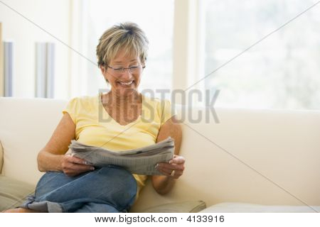 Woman Relaxing With Newspaper In Living Room Smiling