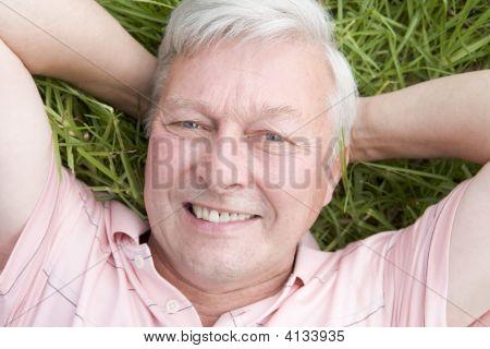 Homem deitado na grama sorrindo