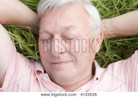 Man Lying In Grass Sleeping