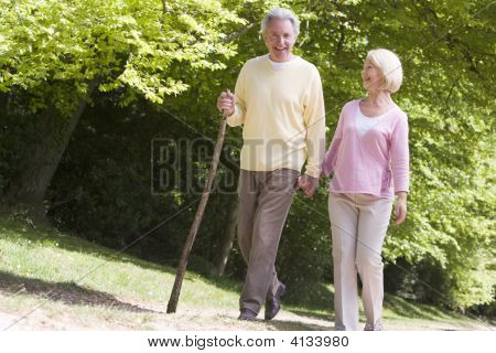 Couples Walking On Path In Park Holding Hands And Smiling