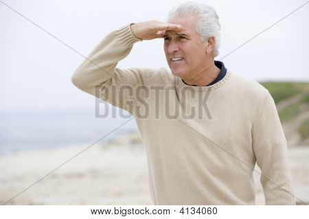 Hombre en la playa mirando hacia fuera con la mano de ojos