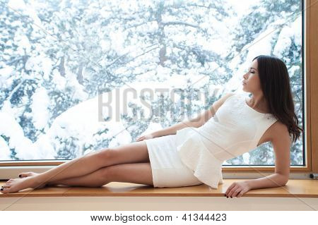 young woman in elegant short dress barefoot sit by window looking at winter snow day