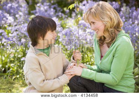 Madre e hijo al aire libre, sosteniendo flores sonriendo