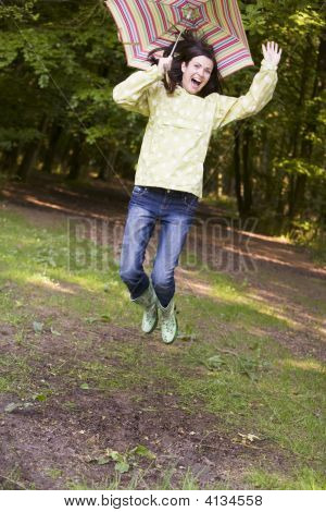 Woman Outdoors Jumping With Umbrella Smiling