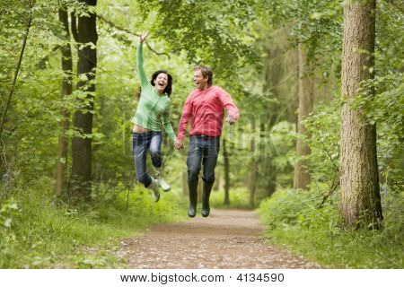 Couples Jumping On Path Holding Hands And Smiling
