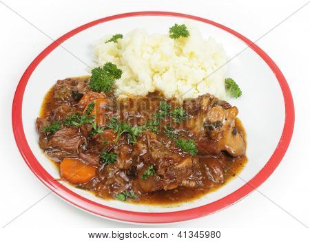 A plate of old-fashioned oxtail stew, served with mashed potato and garnished with English parsley