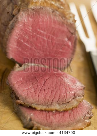 Roast Topside Of British Beef Carved On A Chopping Board