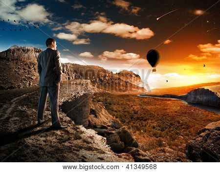 Businessman in mountains looking at sunset