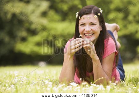 Woman Lying Outdoors With Flowers Smiling