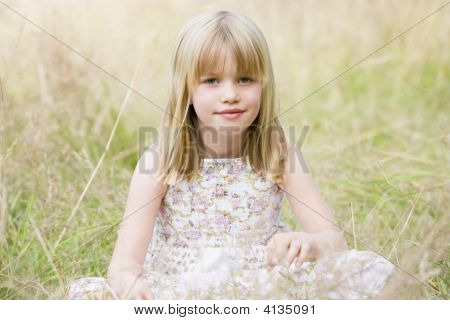 Young Girl Sitting Outdoors Smiling