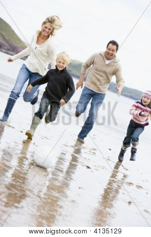 Families Playing Soccer At Beach Smiling