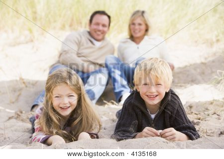 Families Relaxing On Beach Smiling