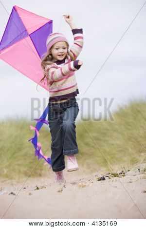 Young Girl On Beach With Kite Smiling