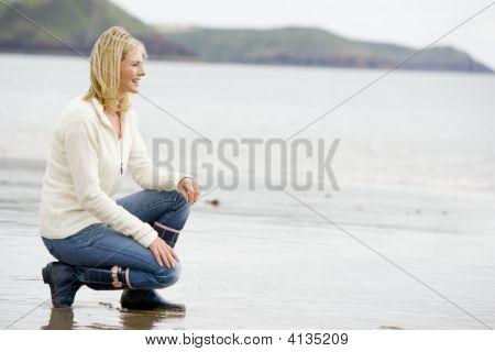 Woman Crouching On Beach Smiling