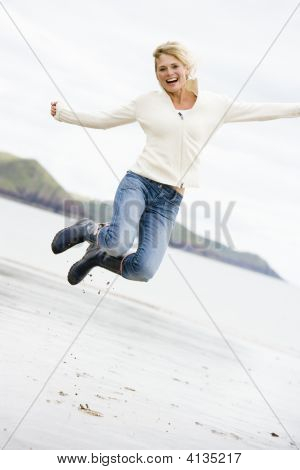 Woman Jumping On Beach Smiling