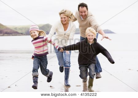 Families Running On Beach Holding Hands Smiling