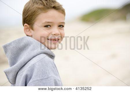Joven parado en Playa sonriendo