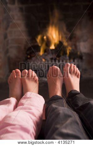 Children'S Feet Warming At A Fireplace