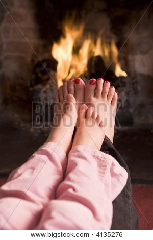 Mother And Daughter'S Feet Warming At A Fireplace