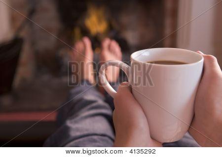 Pies calentamiento en la chimenea con manos sosteniendo café