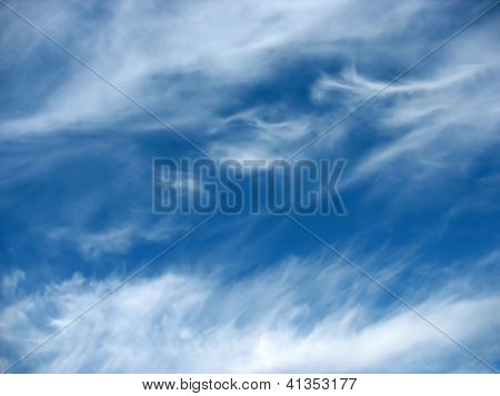 Blue sky background with wavy fleecy clouds