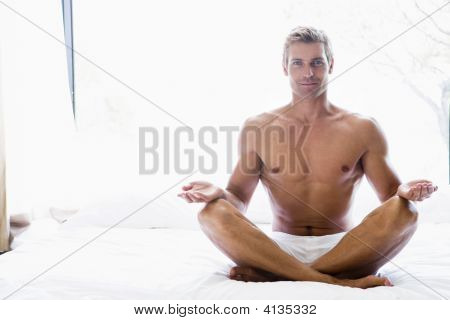 Man Sitting On Bed Doing