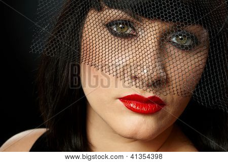 Dramatic portrait of young widow wearing elegant black clothes and in veil.
