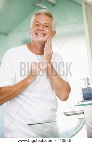 Man In Bathroom Applying Aftershave And Smiling