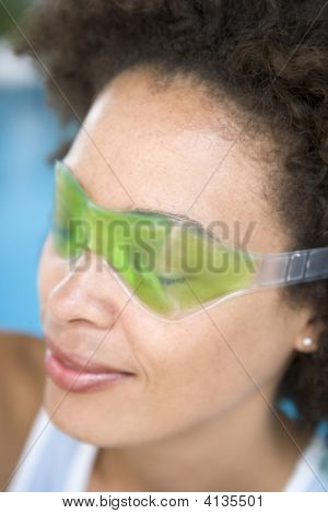 Woman Sitting Poolside Using Eye Mask