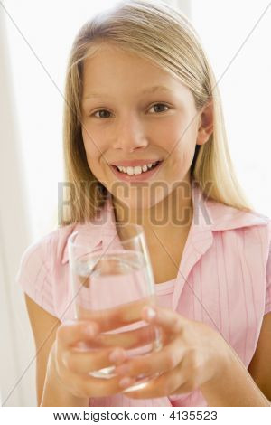 Young Girl Indoors Drinking Water Smiling