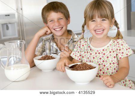 Dos niños en la cocina comiendo Cereal sonriendo