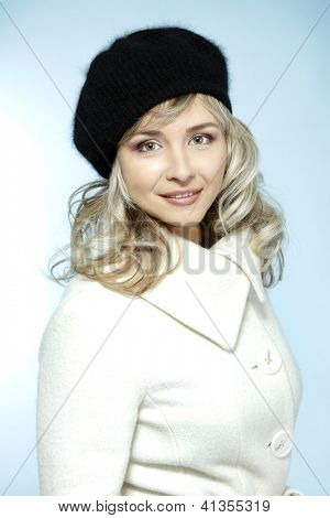 mid adult woman winter portrait, attractive caucasian middle 40 years old woman in coat and hat over blue