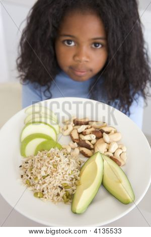 Young Girl In Kitchen Eating Rice Fruit And Nuts