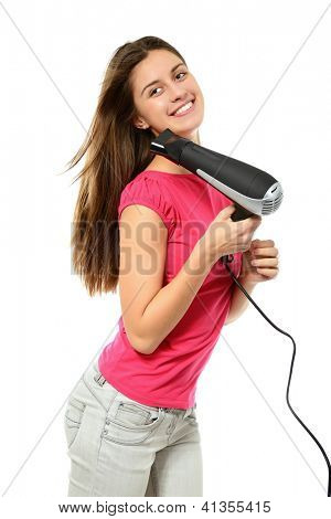 attractive cheerful teenager girl blows dry her hair with hairdryer, over white