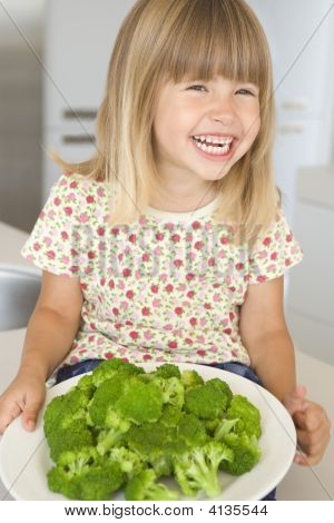 Young Girl In Kitchen Eating Broccoli Smiling