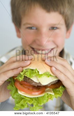 Young Boy Eating Cheeseburger Smiling