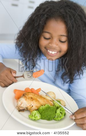 Young Girl In Kitchen Eating Chicken And Vegetables Smiling