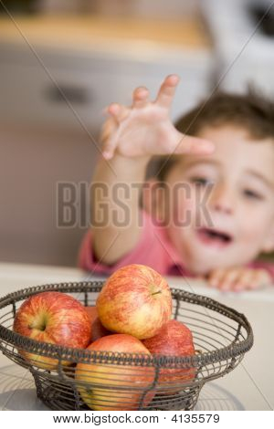 Young Boy In Kitchen Getting Apple Off Counter