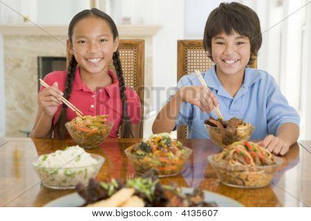 zwei junge Kinder essen chinesisches Essen im Speisesaal lächelnd