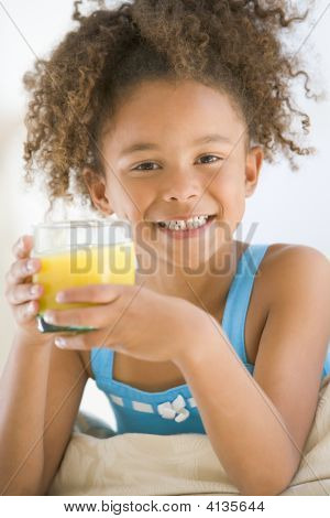 Young Girl Drinking Orange Juice In Living Room Smiling