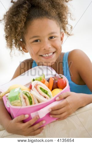 Young Girl holding Lunchpaket in Living Room smiling