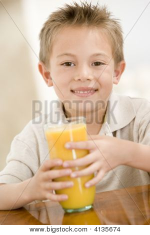 Young Boy Indoors With Orange Juice Smiling