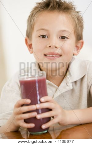 Young Boy Indoors Drinking Juice Smiling