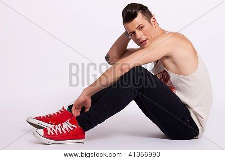 full length portrait of a handsome arrogant young man sitting on the floor over a gray background