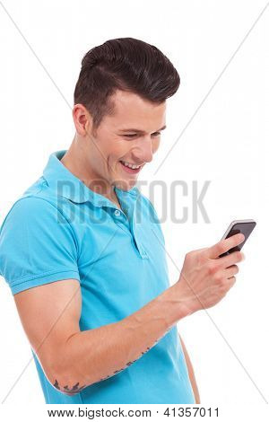 closeup picture of a young casual man reading/writing a text message on his phone and smiling, on white background
