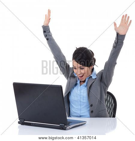 Young woman in office jubilates and wins at desk. Isolated on white background.