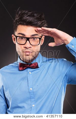casual fashion man making a military salute on dark background