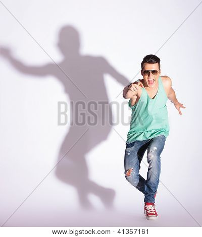 smiling young casual man pointing to the camera on gray background with hard shadow