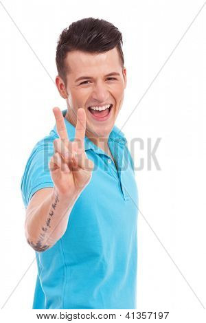 Portrait of young man smiling and showing you victory sign on white background